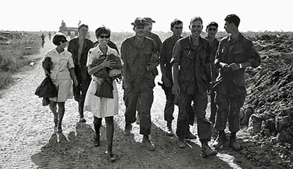 Char McClintic and Judi Wright move toward the perimeter of the Combat Forward base camp. They are accompanied by willing soldiers happy to escort them.